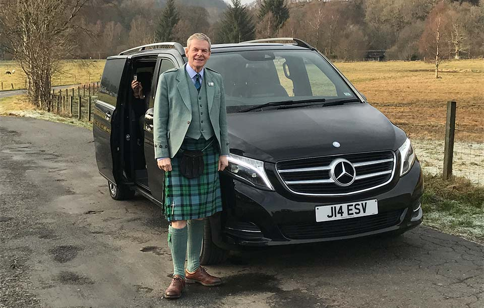 Luxury car Mercedes with tour guide in kilt.